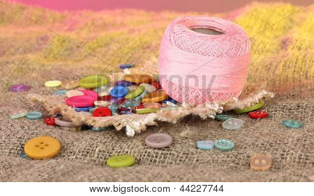 Beautiful buttons and a ball of yarn on a bright background