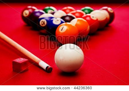 Billards pool game. Cue ball, cue, color balls in triangle, chalk. Red cloth table