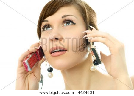 Busy Beautiful Young Woman Talking On Two Cell-phones