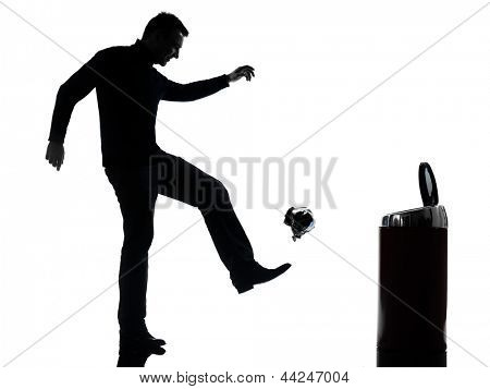 one caucasian man dropping a paper in a trash bin full length in silhouette studio isolated on white background