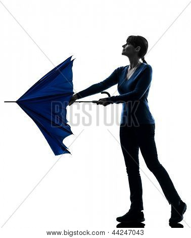one caucasian woman opening closing umbrella  in silhouette studio isolated on white background