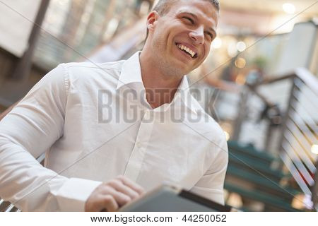 Businessman with tablet computer in hands, blurred background, modern business building