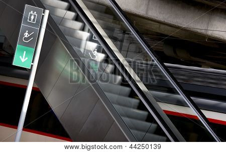 Signpost And Escalators In A Railway Station