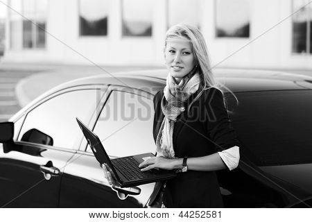Young business woman with laptop against a car