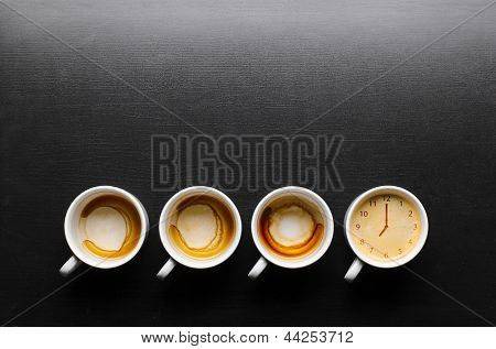 working hours. empty and full cups of fresh espresso with clock sign, view from above