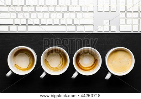 working hours. empty and full cups of fresh espresso with keyboard, view from above