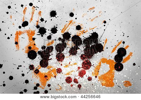Orange hand prints with black ink blots on grey background