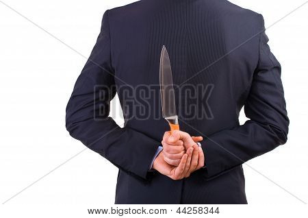 Business man holding knife behind his back.