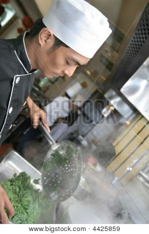Chef Cooking And Holding Pepper Mill