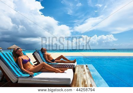 Couple relaxing in chaise lounge at the poolside