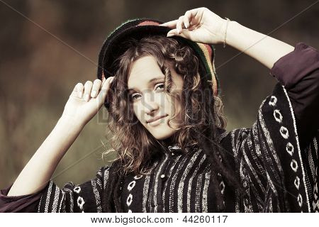 Young rastafarian woman against a nature background