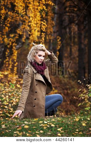 Young blond woman in autumn forest