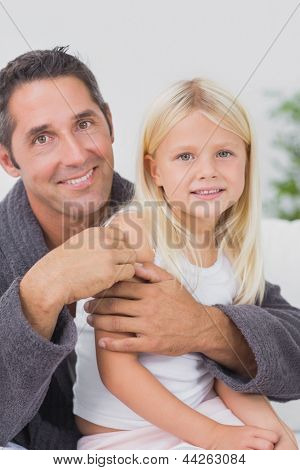 Smiling father hugging his daughter and looking at camera