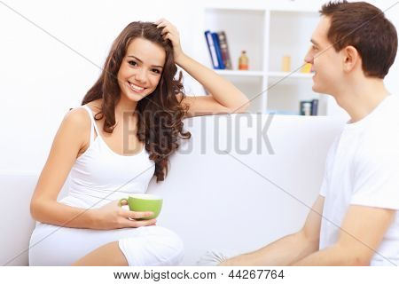 Young happy couple at hone together sitting and talking