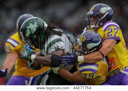 VIENNA, AUSTRIA - JULY 15 RB Tunde Ogun (#1 Dragons) is tackled by LB Simon Blach (#49 Vikings) and LB Marcus Greber (#27 Vikings) on July 15, 2012 in Vienna, Austria.