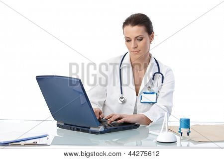 General practitioner sitting at desk, typing on laptop computer, isolated on white.