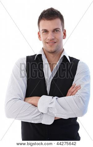 Confident young businessman smiling arms crossed.