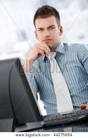 Serious young businessman sitting at desk in bright office, thinking, looking at camera.