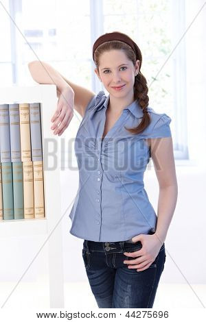 Attractive young woman at home, standing by bookshelf, smiling at camera.