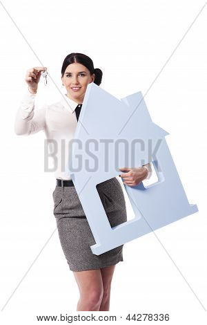 Beautiful businesswoman holding house sign and keys