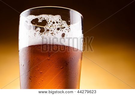 Glass Of Beer With Froth Close Up On A Yellow Background