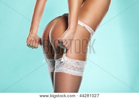 Torso portrait of a slender woman wearing stockings and suspenders displaying her sexy bum