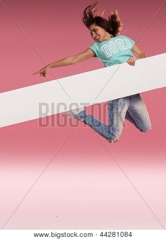 Woman holding a long white banner leaping in the air and pointing down its length against a pink background