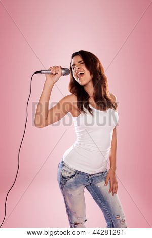 sexy singer holding a microphone wearing white top and jeans