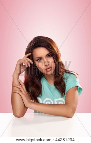 Beautiful thoughtful young woman sitting at a table regarding the camera with a wistful faraway expression against a pink background
