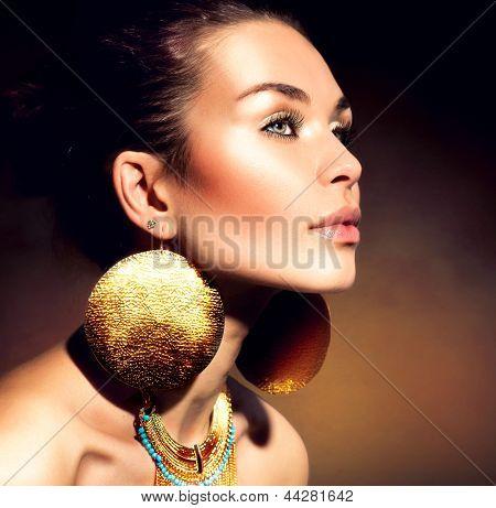 Fashion Woman Portrait. Golden Jewels. Trendy Makeup. Gold Jewellery. Accessories