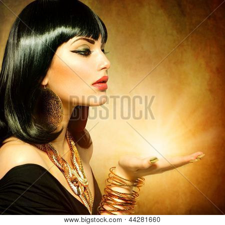 Egyptian Style Woman with Magic Light in Her Hand. Golden Jewels. Egypt Styled Makeup. Gold Light. Jewellery