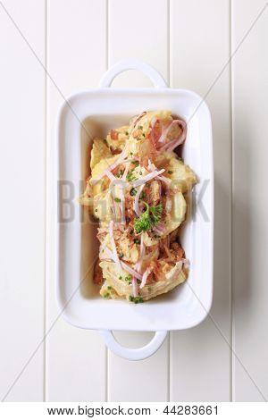 Salada de batata polvilhado com cascas de presunto e carne de porco