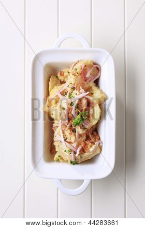 Potato salad sprinkled with ham and pork rinds