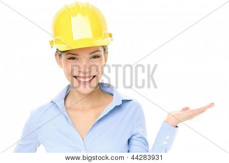 Hard hat engineer or architect woman showing pointing at copy space. Young female mixed race Caucasian / Asian Chinese professional wearing yellow hard hat isolated on white background in studio.