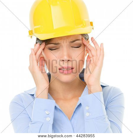 Engineer or architect woman worker having headache migraine stress wearing yellow hard hat. Young female mixed race Caucasian / Asian Chinese professional isolated on white background