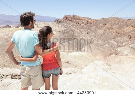 Death Valley tourists people in California enjoying view desert landscape of Zabriskie Point in Death Valley National Park, California, USA. Young couple on travel road trip in United States.