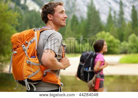 Hikers - people hiking, man looking at mountain nature landscape scenic with woman in background. Happy multicultural young couple in Yosemite National Park, California, USA
