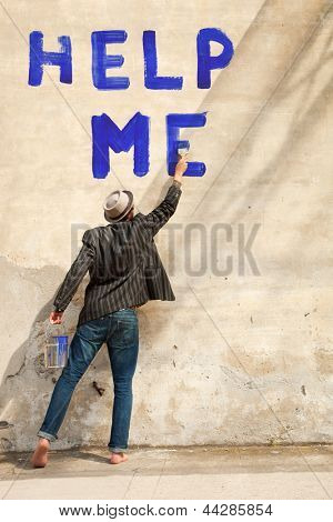 man writes on a wall help me
