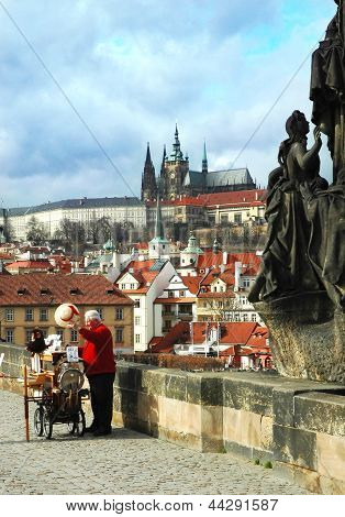 Charles Bridge in Prague. A Man Offers Music From Hand Operated Music Box In Exchange For Money
