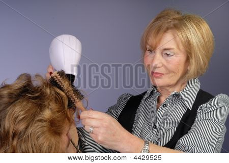 Attractive Older Lady Hair-stylist Blow Dries Hair