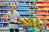 stock photo of local shop  - a woman is overwhelmed with the wide range in the supermarket when shopping - JPG