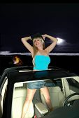 pic of tubetop  - pretty blond girl standing in car sunroof on the beach at night - JPG