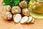 picture of jerusalem artichokes  - One cut and a few whole tubers of Jerusalem artichoke parsley and a bottle of vegetable oil on a wooden board - JPG