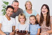 Smiling family celebrating with birthday cake
