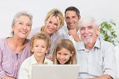 Family smiling in front of a laptop screen in the living room