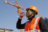 stock photo of vest  - Engineer with safety vest drinking water under construction - JPG