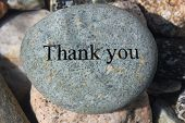 stock photo of give thanks  - Positive reinforcement word Thank You engrained on a rock - JPG