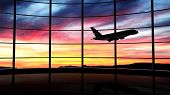stock photo of terminator  - Airport window with airplane flying at sunset - JPG