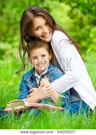 Mum and son with book sitting on green grass in green park. Concept of happy family relations and carefree leisure time