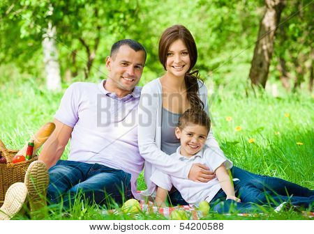 Happy family of three has picnic in green park. Concept of happy family relations and carefree leisure time